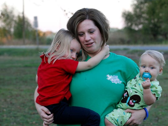 "FILE - In this Nov. 11, 2010 file photo, Courtney Kemp, 27, holds her daughters Kaylee Kemp, 3, left, and Madisson Kemp, 9 months, in Jonesville,  Courtney's husband Roy Wyatt Kemp, 27, died in the Deepwater Horizon oil rig explosion. The film, ""Deepwater Horizon"" is stirring mixed emotions for family members of the 11 men who died in the blast. While their reactions to the movie vary, many relatives share a hope that the film will remind people about the disaster's human toll. (AP Photo/Gerald Herbert)"