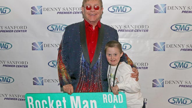British pop star Sir Elton John greets 10-year-old Evan Snow of Baltic before Friday's concert in Sioux Falls.