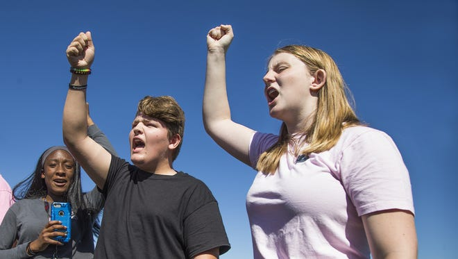 """Students Zane Collins, 14, left, and Ella McGorray, 14, right, freshman at Mountain Ridge High School in Glendale, Arizona, chant """"enough is enough"""" as they demand more gun control after the massacre at Marjory Stoneman Douglas High School in Florida.  Hundreds of students met on the football field to protest."""