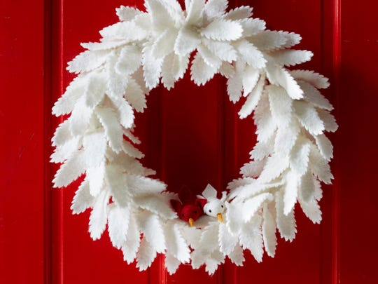 In this photo provided by West Elm, felt feathers in warm winter white give a sculptural quality to a soft wreath. Besides the beloved evergreen standard, each year sees more and more inventive versions of the wreath. There are regional variations in unexpected materials; square wreaths and star-shaped wreaths; wreaths in indigo, pale pink and other non-traditional colors; and more. (AP Photo/West Elm)