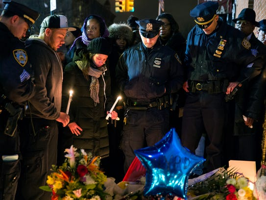 Police officers and other mourners stand in silence,