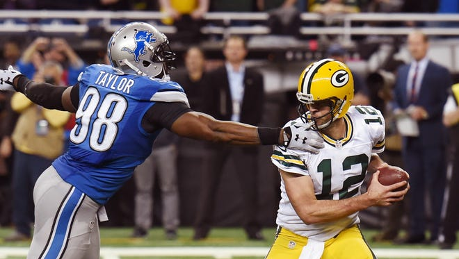 Detroit Lions defensive end Devin Taylor reaches for Green Bay Packers quarterback Aaron Rodgers and is called for a facemask on what would have been the game's final play Thursday, Dec. 3, 2015, in Detroit.