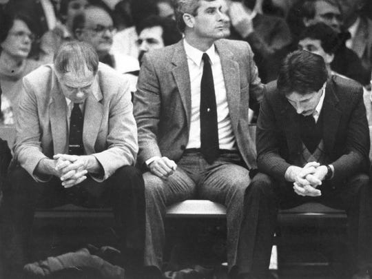 Tom Izzo, right, and Jud Heathcote, left, strike the same pose on the bench of a Michigan State game in 1985. A year later, Heathcote pushed Izzo to go to Tulsa to be a full-time assistant coach. Seven weeks later, when Mike Deane, center, left to become coach at Siena, Heathcote hired Izzo back. He's been at MSU ever since.