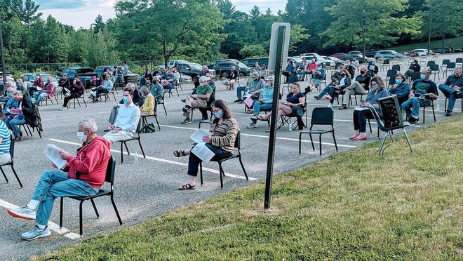 Charlton residents listen to articles on a town meeting warrant during Monday's meeting held outside in the Charlton Middle School parking lot due to coronavirus pandemic.