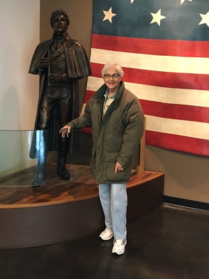 """Shirley Carole Isham, a great great great granddaughter of Francis Scott Key, stands next to a statue of the man who wrote """"The Star-Spangled Banner."""""""