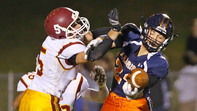 Harrison's Jonathon Laguire makes a one-handed catch while defended by McCutcheon's Cole Williams in the Class 5A Sectional 11 Friday, October 28, 2016, in West Lafayette. McCutcheon defeated Harrison 29-12.