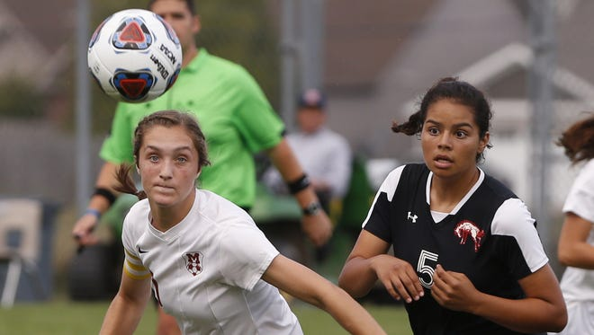 Audrey Walker of McCutcheon works to get past Guadalupe Villegas of Lafayette Jeff in the girls soccer sectional Tuesday, October 3, 2017, at Harrison High School.