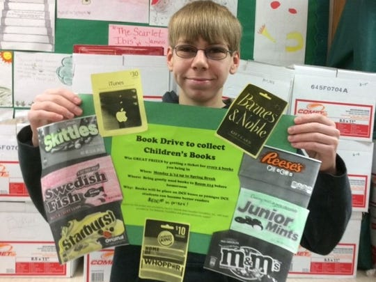 Tyler Corazalla displays promotional signs for the book drive.