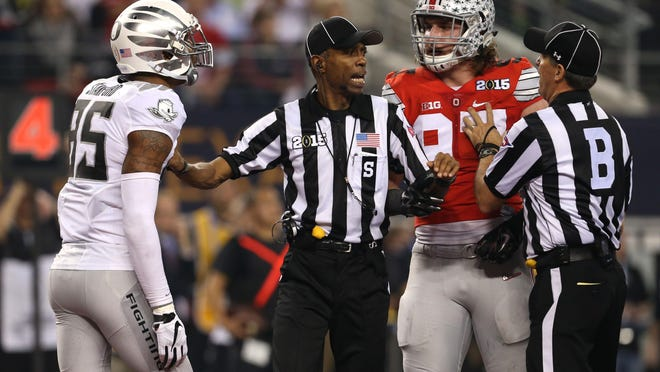 An official pushes Oregon's Dwayne Stanford, left, and Ohio State's Joey Bosa apart after an altercation after the Ducks failed to convert on a fourth-down attempt in the red zone during the first half of the inaugural College Football Playoff championship game on Jan. 12, 2015. Ohio State won 42-20. [Chris Pietsch/The Register-Guard] - registerguard.com
