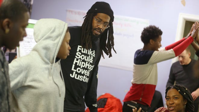 """Shawn Brown, program coordinator at Teen Empowerment, works with his youth group in 2016 on a variety of exercises including a fun """"human obstacle course"""" exercise using only sounds to direct each other. (Photo: SHAWN DOWD/@sdowdphoto/, STAFF PHOTOGRAPHER)"""