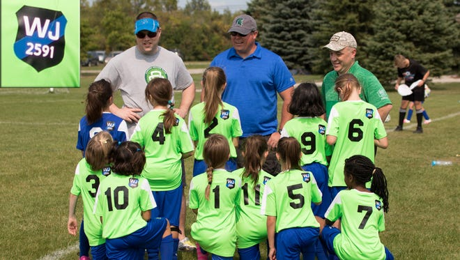 The Dolphins, who play for the Canton Soccer Club in the U9 girls division, show support for Detroit police officer Waldis Johnson by wearing special patches on their jerseys.