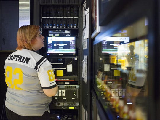 Guest experience captain Alyssa Strickler, 21, of West Manchester Township, checks the program guide before changing the channel on one of the more than 50 televisions mounted throughout the restaurant.