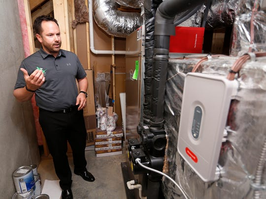 Grant Giese of Green Goose Homes talks about geothermal unit in his home Friday, May 12, 2017, at 693 Appaloosa Trail in West Lafayette. Giese estimates that the geothermal unit pays for itself over the course of five years. Giese incorporates several environmentally friendly features in every Green Goose Home. Giese said all the homes he has built are certified as green.