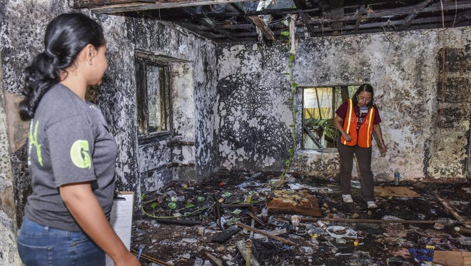 Team leader Margaret Hattori-Uchima, right, and University of Guam School of Nursing and Health Sciences professor Yvette Paulino search a burned-out structure for any signs of occupancy during a homeless count survey in January 2015.