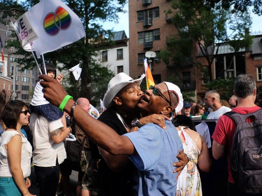 A couple kisses to celebrate the US Supreme Court's historic decision on same sex marriage during a rally outside the Stonewall Tavern in the West Village in New York on June 26, 2015. The US Supreme Court ruled on June 26, that gay marriage is a nationwide right, a landmark decision in one of the most keenly awaited announcements in decades and sparking scenes of jubilation.