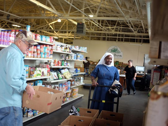 At the Food Bank for Monterey County on Tuesday, Louie Rothstein, left, with St. Vincent de Paul-Madonna Del Sasso Church in Salinas, and Sister Benedicta, with St. Francis Xavier Church in Seaside, shop for staples for their respective food programs.