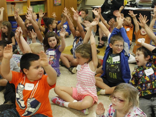 "Students at Boswell Elementary School raise their hands Friday, Sept. 15, 2015, during a presentation by Yvette Quarles Chatman. Chatman taught students about African-American history using her book, ""They Dared."""