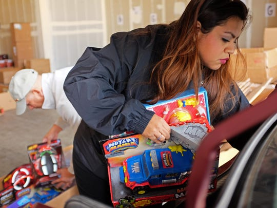 Una Andazola and Larry Sanchez categorize toys donated to the 2015 Toys for Tots campaign.