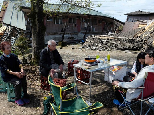 Residents rest next to houses which collapsed in the recent earthquakes in Mashiki in Kumamoto prefecture on April 17, 2016.