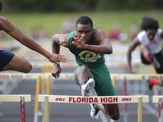 Lincoln's Vincent Johnson battles a stiff headwind in the 110 hurdles, finishing as district runner-up.