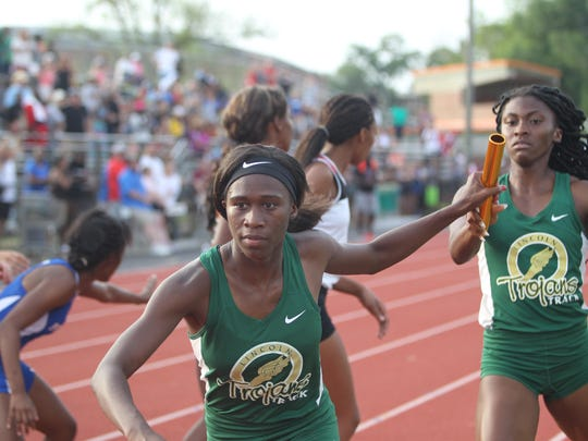 Lincoln's TeJyrica Robinson takes the baton pass from Tamani Wilson during the 4x400 relay, which the Trojans won to capture a Region 3-3A title and finalize a team victory, which was the first ever regional title for Lincoln's girls track program.