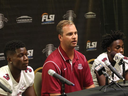 Chiles head football coach Garrett Jahn addresses the media Tuesday with seniors Kris Reed, left, and Shane Sanders by his side.