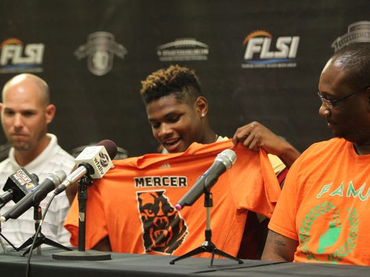 Florida High linebacker Cam Brown, alongside his father and Seminoles coach Jarrod Hickman, commits to Mercer University on Tuesday during 4QuartersOnline Media Day.