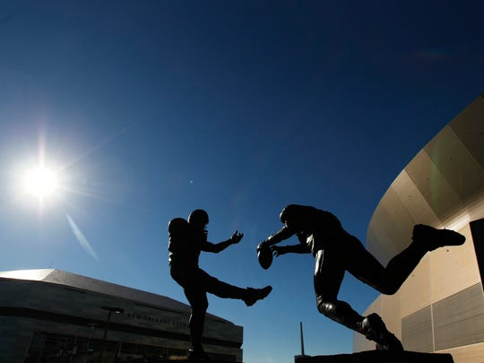"""FILE - This Sept. 25, 2006 file photo shows the bronze statue titled """"Rebirth,"""" outside the Mercedes-Benz Superdome, which depicts former New Orleans Saint Steve Gleason blocking a punt against the Atlanta Falcons during the first Monday Night Football game, after the Superdome re-opened after Hurricane Katrina. When the New Orleans Saints host rival Atlanta on Monday night, it'll mark the 10-year anniversary of the stadium's reopening, and a victory over the Falcons that symbolized a city's determination to rebuild from one of the worst natural disasters in American history. (AP Photo/Gerald Herbert, File)"""
