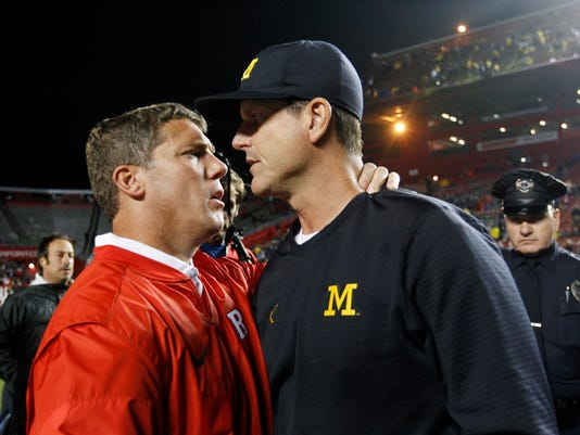 Michigan head coach Jim Harbaugh, right, greets Rutgers head coach Chris Ash at the end of an NCAA college football game Saturday, Oct. 8, 2016, in Piscataway, N.J. (AP Photo/Mel Evans)