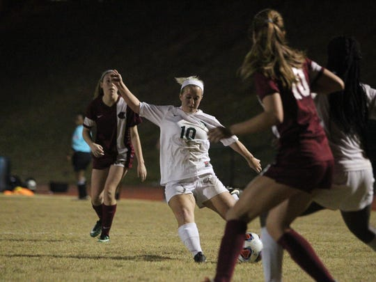 Lincoln junior Erica Driver fires a shot during Wednesday's District 2-4A semifinal against Lincoln. Driver made the winning goal in a penalty-kick shootout as the Trojans advanced.