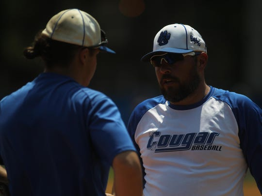 Godby baseball coach Jayson Strickland talks with third baseman Seth Sapp, a recent call-up from JV who has helped secure infield play.