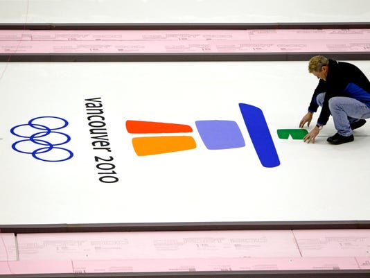 FILE - In this Tuesday, Feb. 9, 2010 file photo, Hans Wuthrich, chief ice-maker from Gimley, Manitoba, places the Olympic logos at the Vancouver Olympic Center before the 2010 Winter Olympic Games, in Vancouver, British Columbia. One athlete tested positive for doping in reanalysis of 1,195 samples from the 2010 Vancouver Olympics, it was announced on Monday, Oct. 9, 2017. The International Olympic Committee says three positive tests in total all came from the same athlete. That athlete was not identified. The IOC says urine samples reanalyzed included from all medalists and all Russian athletes. (AP Photo/Gerry Broome, file)