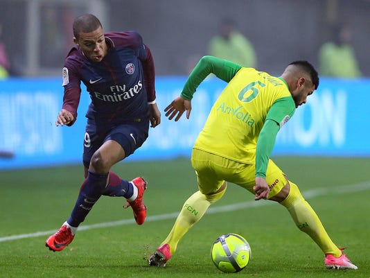 PSG's Kylian Mbappe challenges for the ball with Nantes' defender Lima, right, during their French League One soccer match in Nantes, western France, Sunday, Jan. 14, 2018. (AP Photo/David Vincent)