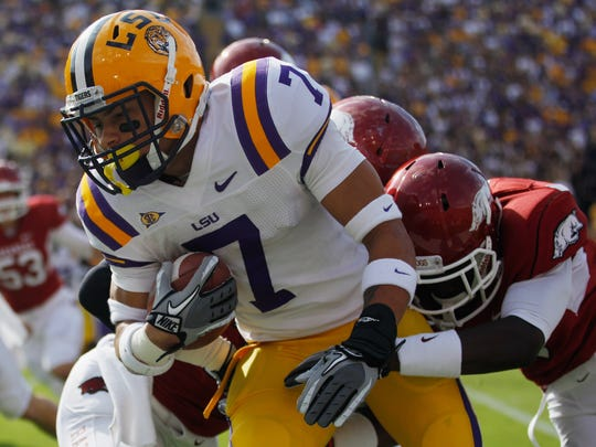 BATON ROUGE, LA - NOVEMBER 25:  Kick returner Tyrann Mathieu #7 of the LSU Tigers returns a punt for seven yards as he is tackled by Marquel Wade #1 of the Arkansas Razorbacks at Tiger Stadium on November 25, 2011 in Baton Rouge, Louisiana.  (Photo by Chris Graythen/Getty Images)
