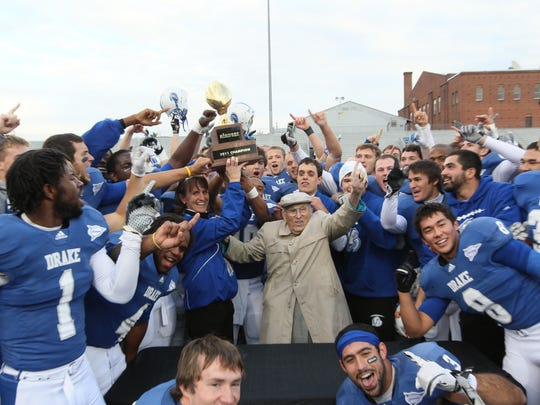 "Paul Morrison celebrates Drake University's 2011 Pioneer Football League title with members of the Bulldog football team and athletic director Sandy Hatfield Clubb. ""He's not a guy who is going to get emotional very often, but you can tell it's important to him,"" said former basketball player Adam Emmenecker."