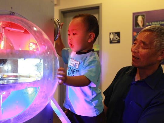 David Liu, left, and Wei Liu check out an exhibit at the Ann Arbor Hands-On Museum. The museum has more than 250 interactive science exhibits and attracts more than 250,000 visitors every year.