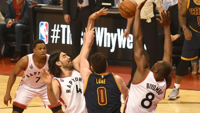 Cleveland Cavaliers forward Kevin Love (0) reaches for a rebound between Toronto Raptors forward Luis Scola (4), center Bismack Biyombo (8) in Game 3.