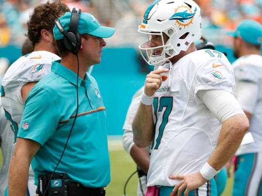 FILE - In this Oct. 16, 2016, file photo, Miami Dolphins quarterback Ryan Tannehill (17) talks to coach Adam Gase during an NFL football game against the Pittsburgh Steelers in Miami Gardens, Fla. The Miami Dolphins have been awful on the road, and that must change if they're to make the playoffs. Two of their final three games are away from Miami, including Sunday, Dec. 16, 2018 at Minnesota, and they likely need a sweep to earn an AFC wild card berth.(AP Photo/Wilfredo Lee, File)