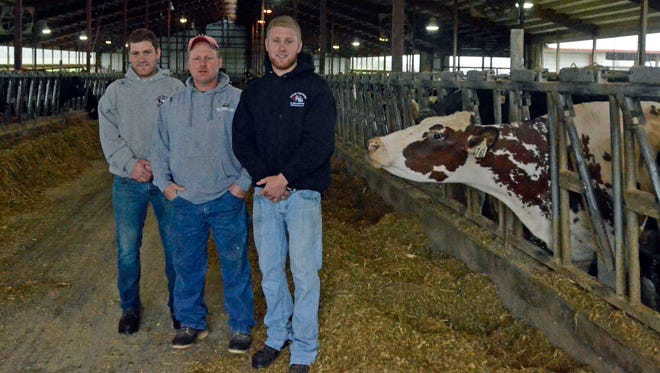 From left, Austin, Mark and Stetson McCulley gather inside the barn at their rural Clarks Mills dairy farm.