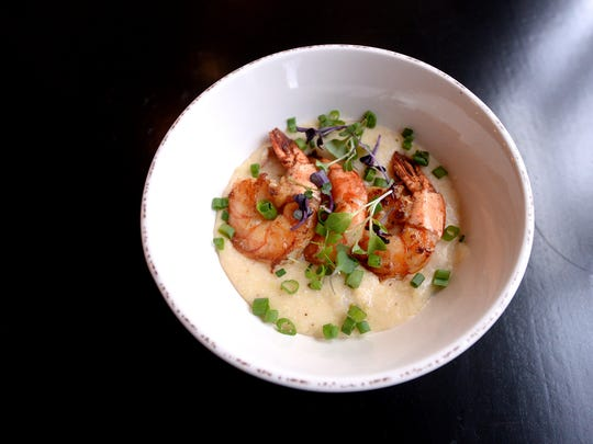 The Creole's shrimp and grits sits on a table at the