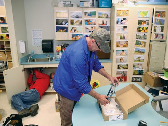 Bremerton School District general maintenance technician Pete Mullen gets a new faucet to install at Crownhill Elementary School in Bremerton.