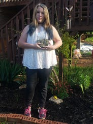 Ryleigh Taylor, 11, stands with her trilobite fossil,
