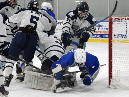Colin Goleniak (71) of the Salem Rocks battles with Mona Shores players during Saturday's game while Matt Schaumburger (background) chips the puck into the goal.