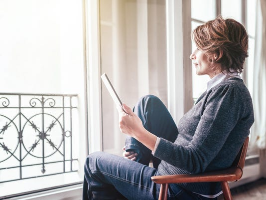 beautiful  french woman reading on digital tablet in Paris apartment