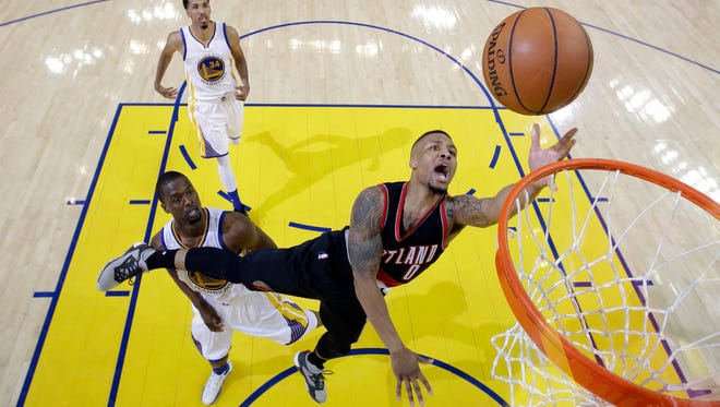 Portland Trail Blazers' Damian Lillard (0) drives past Golden State Warriors' Harrison Barnes, bottom left, and Shaun Livingston (34) during the second half in Game 1 of a second-round NBA basketball playoff series, Sunday, May 1, 2016, in Oakland, Calif. Golden State won 118-106. (AP Photo/Marcio Jose Sanchez)