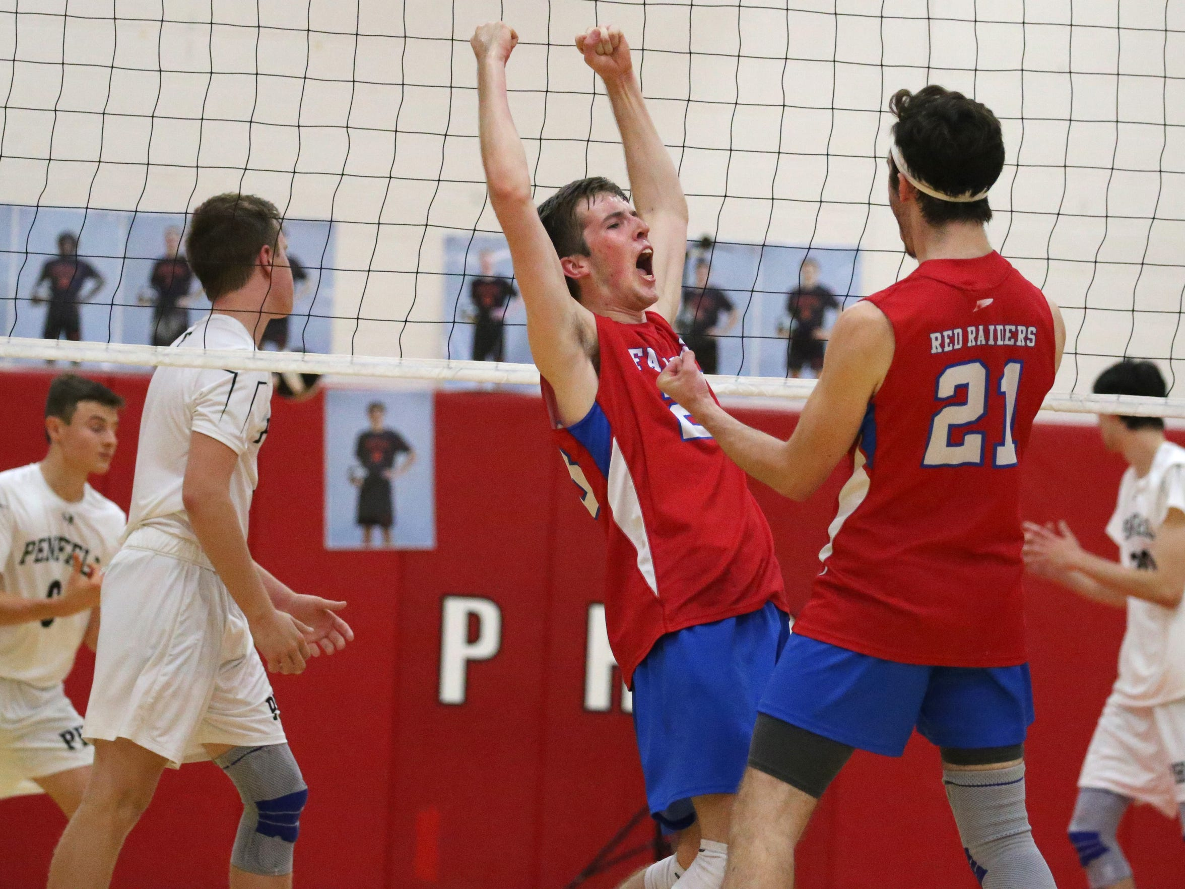 Fairport's Ryan Parker, left, celebrates his point with teammate Matt Beiter, right, in the opening set during their matchup Monday, Sept. 17 at Penfield High School.