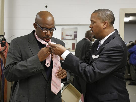 Eusi Saddyk, left, a member of the local Urban League's SOAR program in 2012, is taught how to tie his tie by the Urban League's Rahman Shabazz at the Suit Yourself Men's Clothing Closet.