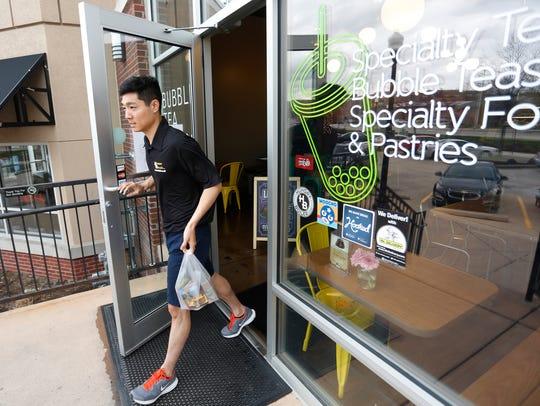 HungryBoiler driver Eric Koo picks up bubble tea from