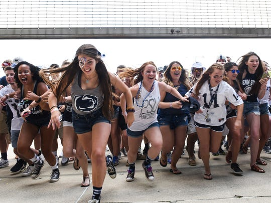 Students rush into the stadium after the gates opened up before the start of the Penn State home opener against Kent State on Saturday, Sept. 3, 2016.
