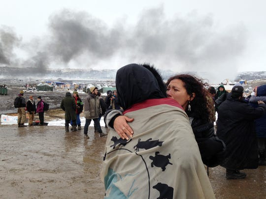 A couple embraces as opponents of the Dakota Access pipeline leave their main protest camp Wednesday.